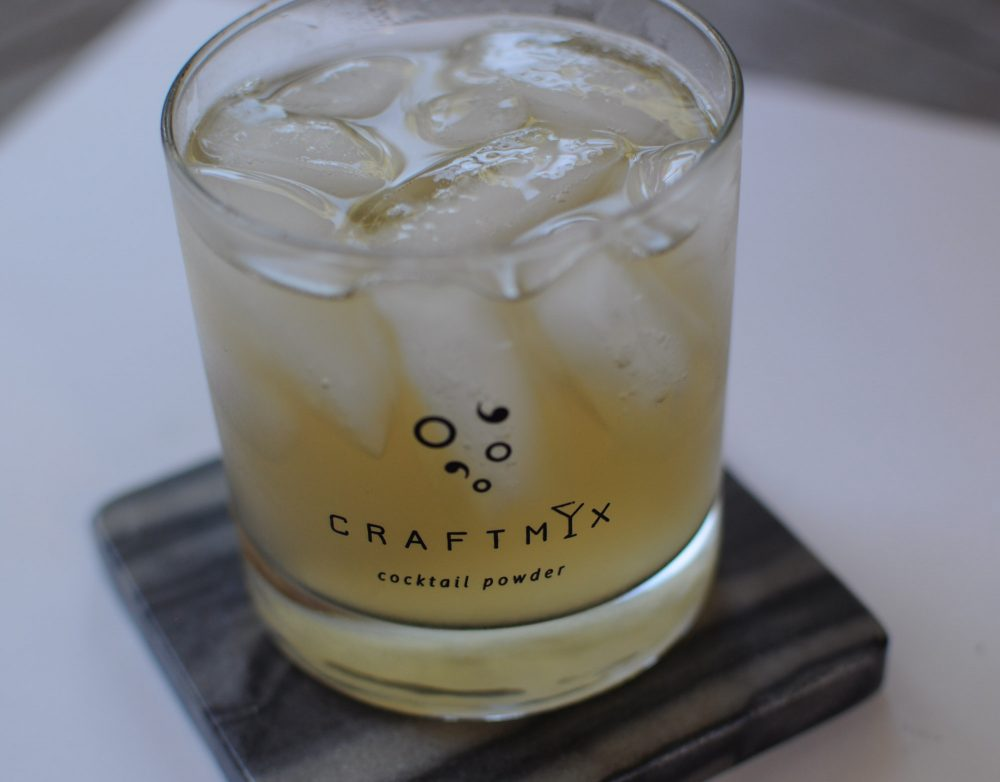 Whiskey Sour cocktail in a cocktail glass, on a black and white marble coaster